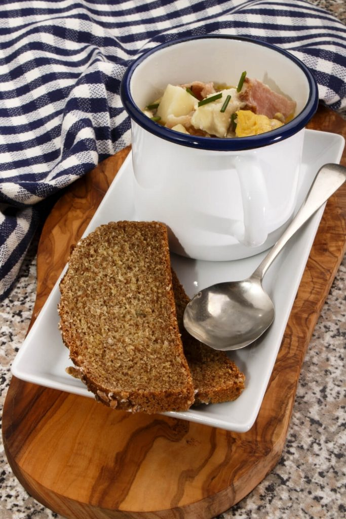 A picture of seafood chowder served in a cup with two slices of Irish soda bread presented on a wooden tray