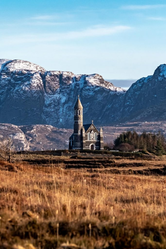 A picture of brown grasses leading towards Dunlewey Church and the Derryveagh Mountains of Donegal in the background