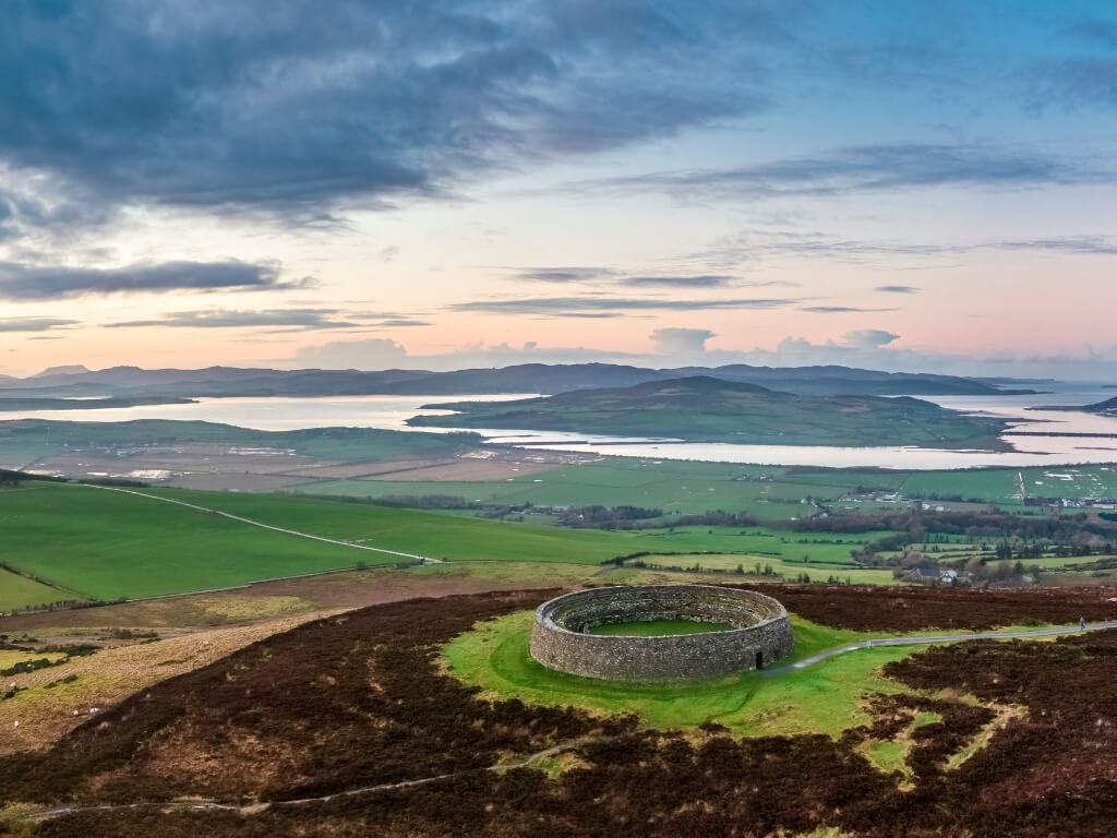 A picture of the Grianan of Aileach ring fort on a hill in Donegal with a sea inlet and coastline in the background