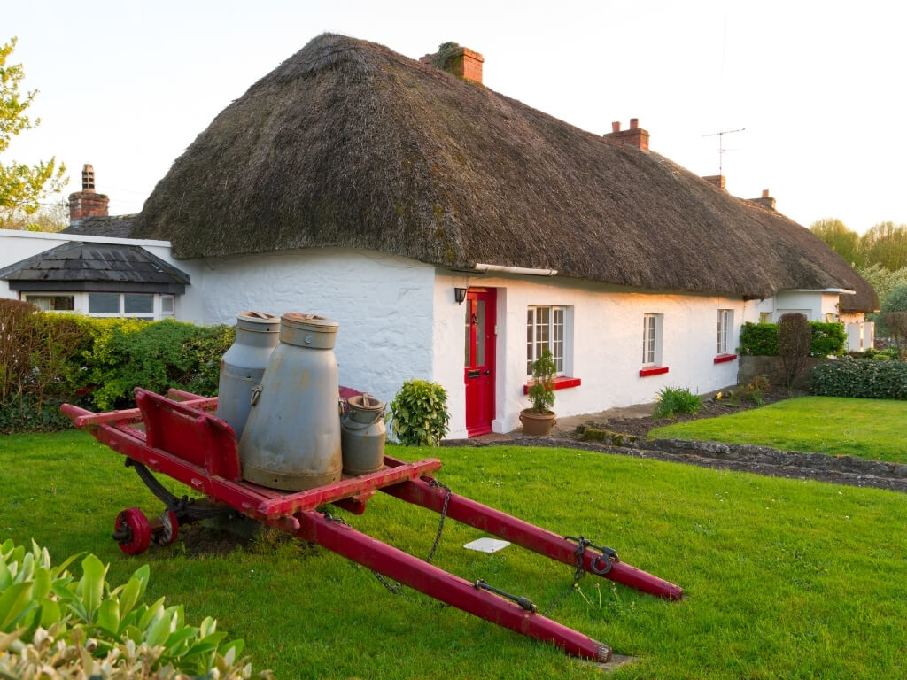 A picture of a traditional house with thatched roof in Ireland and an old red cart with old milk pails on it