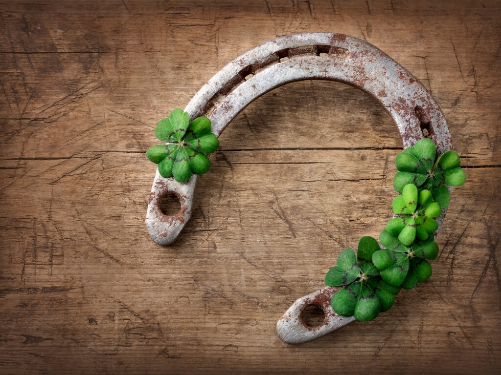 A picture of a horseshoe on wood with a few shamrocks on it