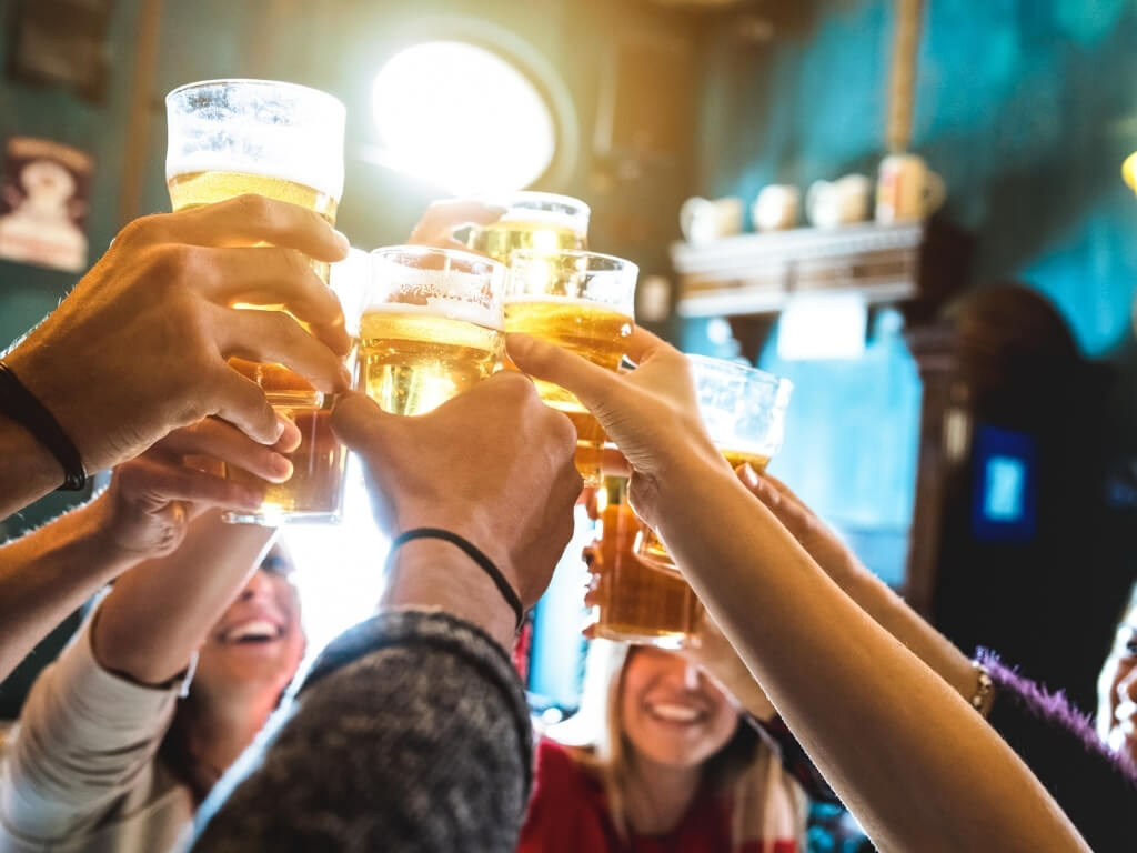 A group of people in a pub raising their pint glasses in a cheers motion