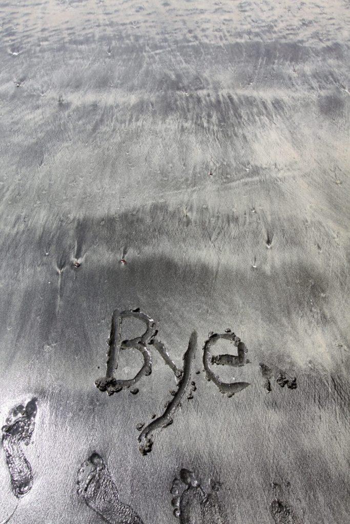 "The word ""bye"" written in sand on a beach"