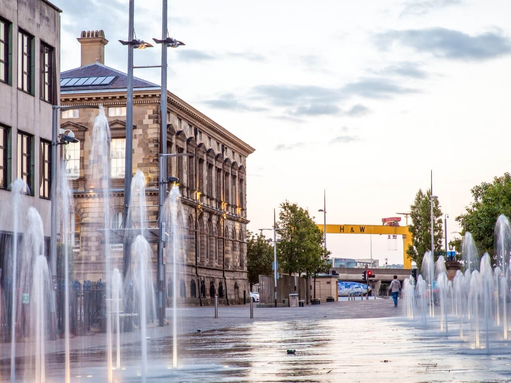 A picture of a water feature in Belfast with the H&W iconic yellow lifts in the background