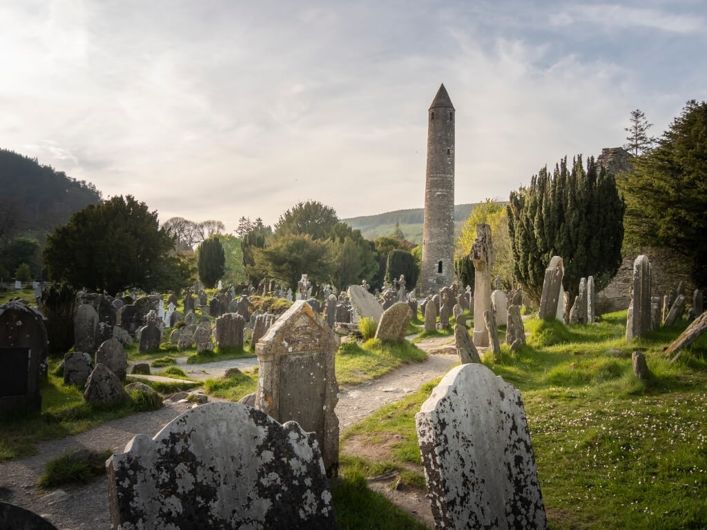 A picture of the round tower and graveyard at the monastic site of Glendalough in County Wicklow, Ireland