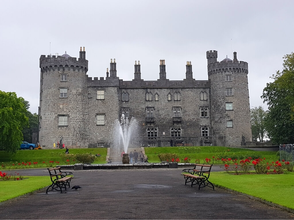 A picture of Kilkenny Castle with a fountain in front