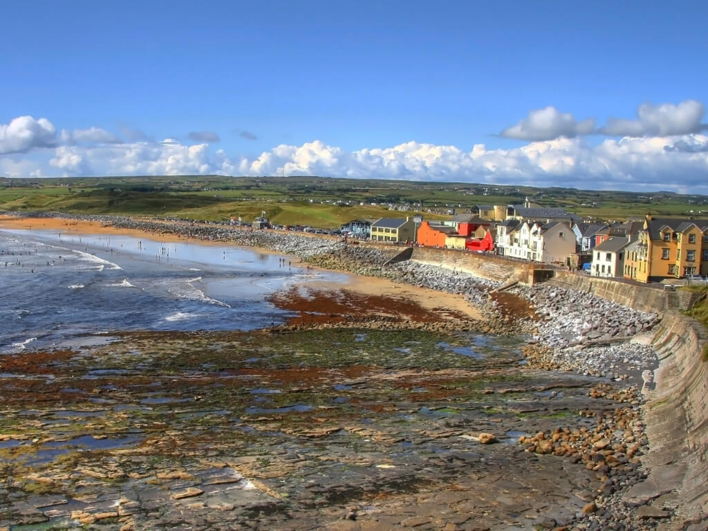 A picture of the stony shoreline with the tide out at Lahinch in County Clare