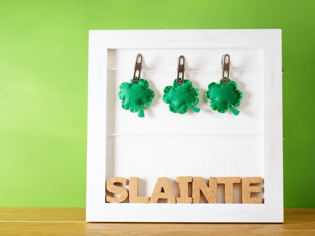 A picture of a white frame with stitched felt shamrocks on pegs at the top and cork letters on the bottom spelling out Slainte