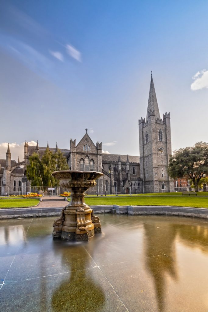 A picture of St Patrick's Cathedral Dublin with a fountain in front with blurred reflections of the cathedral in the water