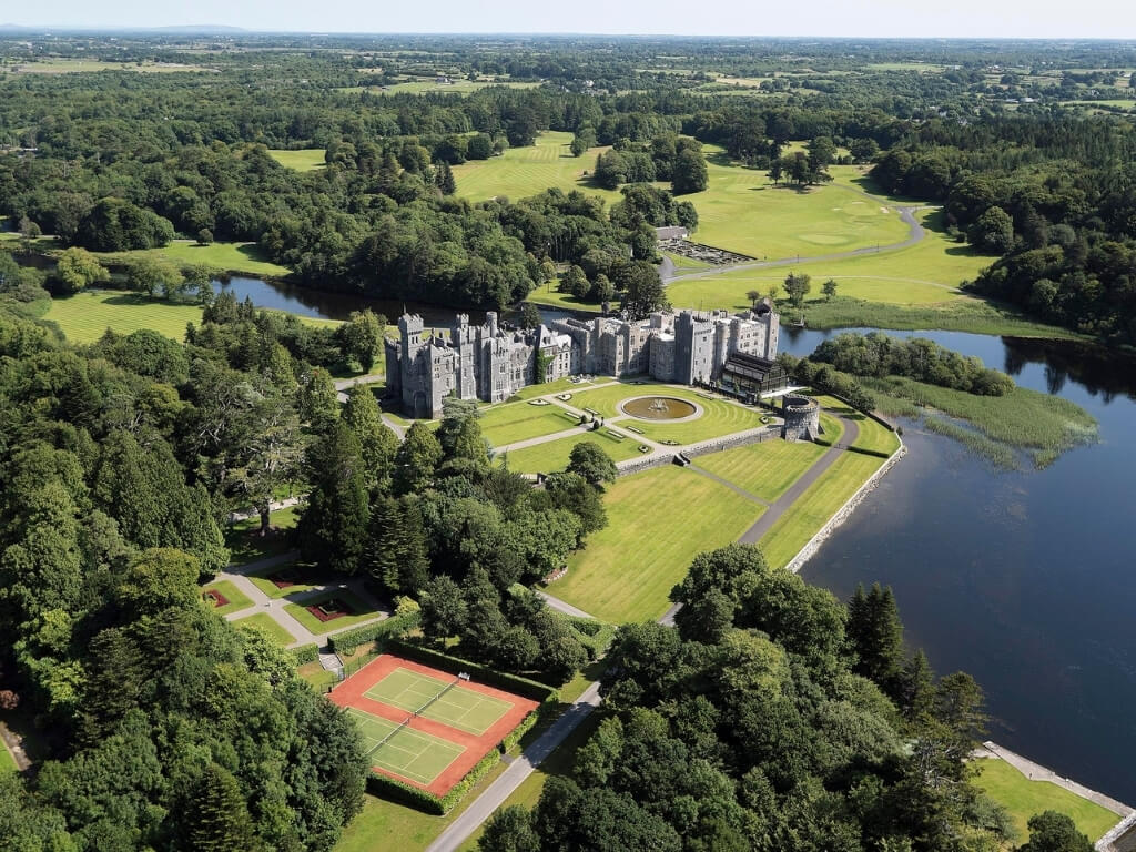 An aerial picture of Ashford Castle with the lake beside it to the right
