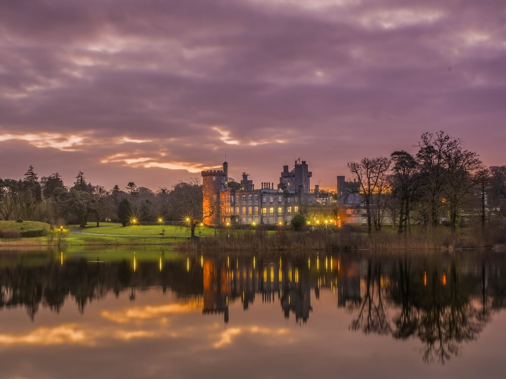 A picture of Dromoland Castle at dusk lit up with the lake in front of it reflecting the castle