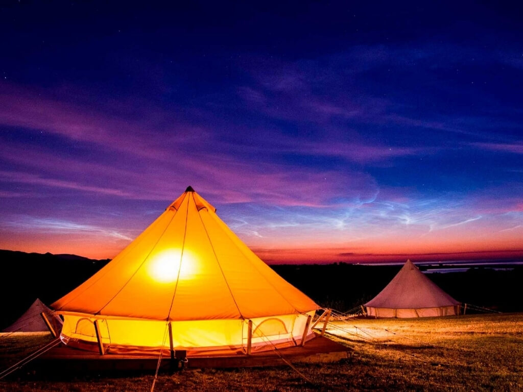 A picture of some of the bell tents at Knockrobin Glamping lit from within at night