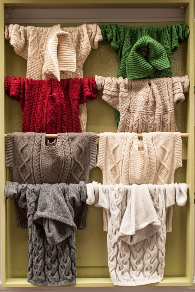 A picture of some clothes rails with Aran jumpers displayed on it