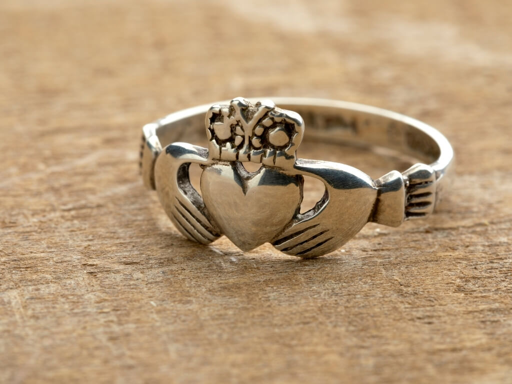 A picture of a silver Claddagh ring on a wooden surface