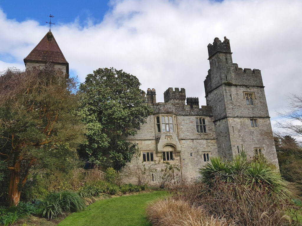 A picture of Lismore Castle in Waterford with green grass and plants leading to the castle building