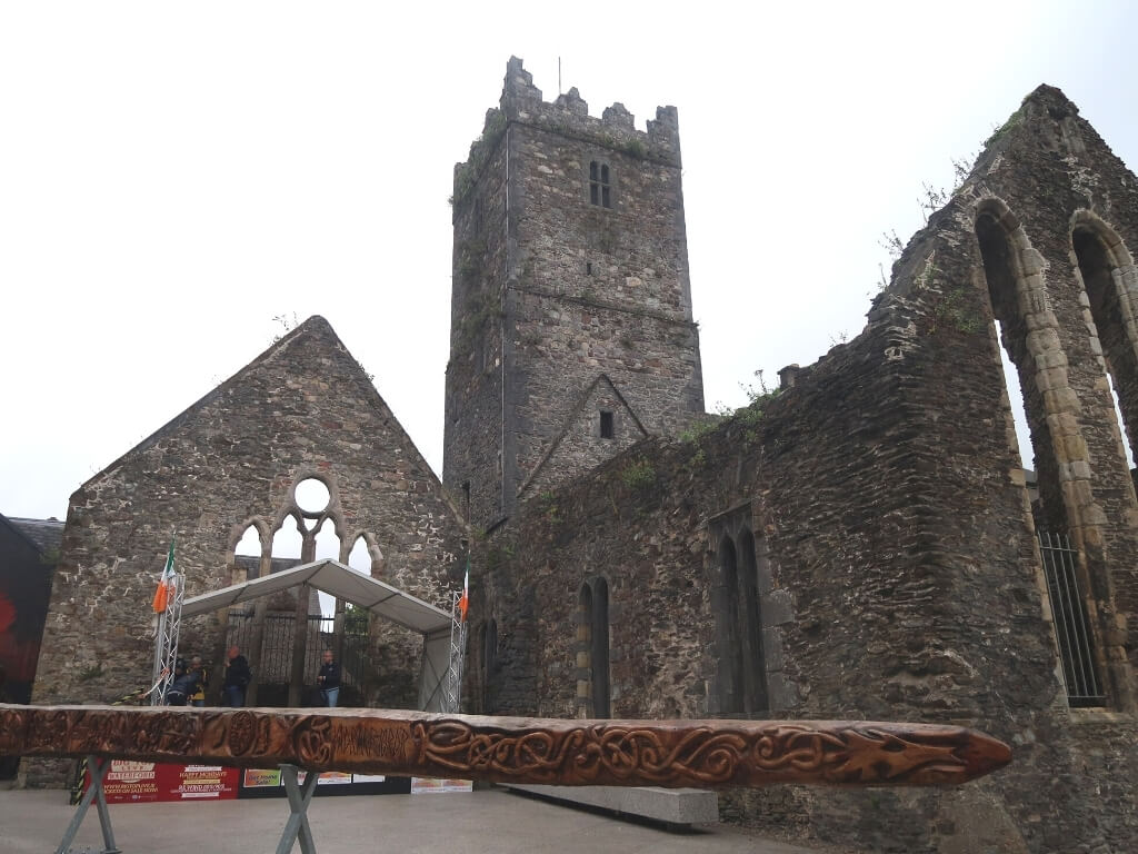A picture of the ruins of a cathedral and a piece of carved Viking wood in Waterford City