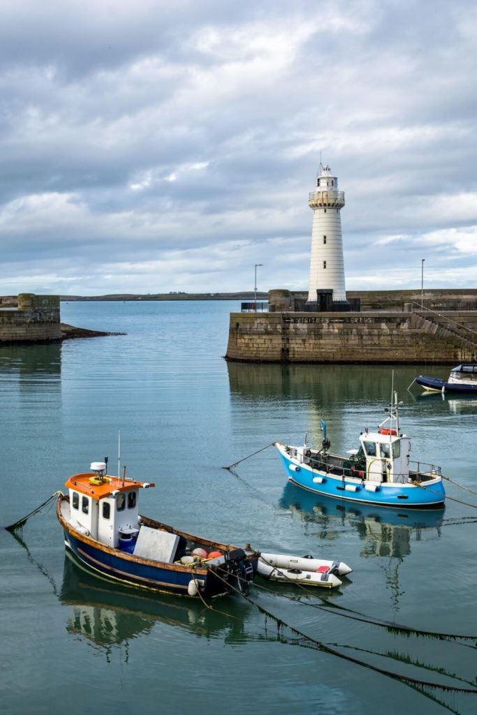 A picture of the Donaghadee Lighthouse at the end of the harbour wall with boats on the water in the foreground