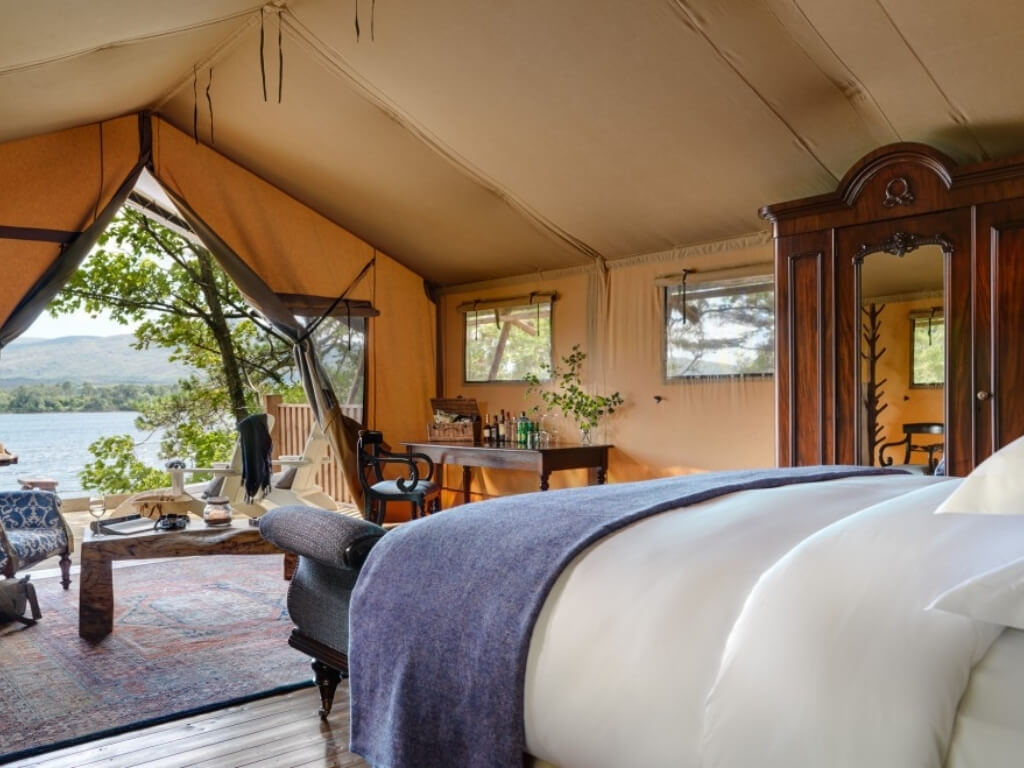 A picture of the interior of a safari tent, looking out at the shoreline at Dromquinna Manor Glamping, Kerry