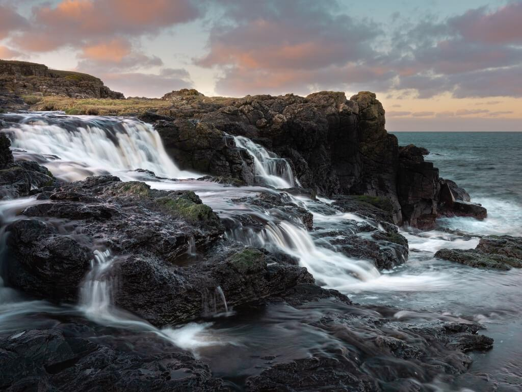 A picture of the water cascading to the sea at the Dunseverick Waterfall