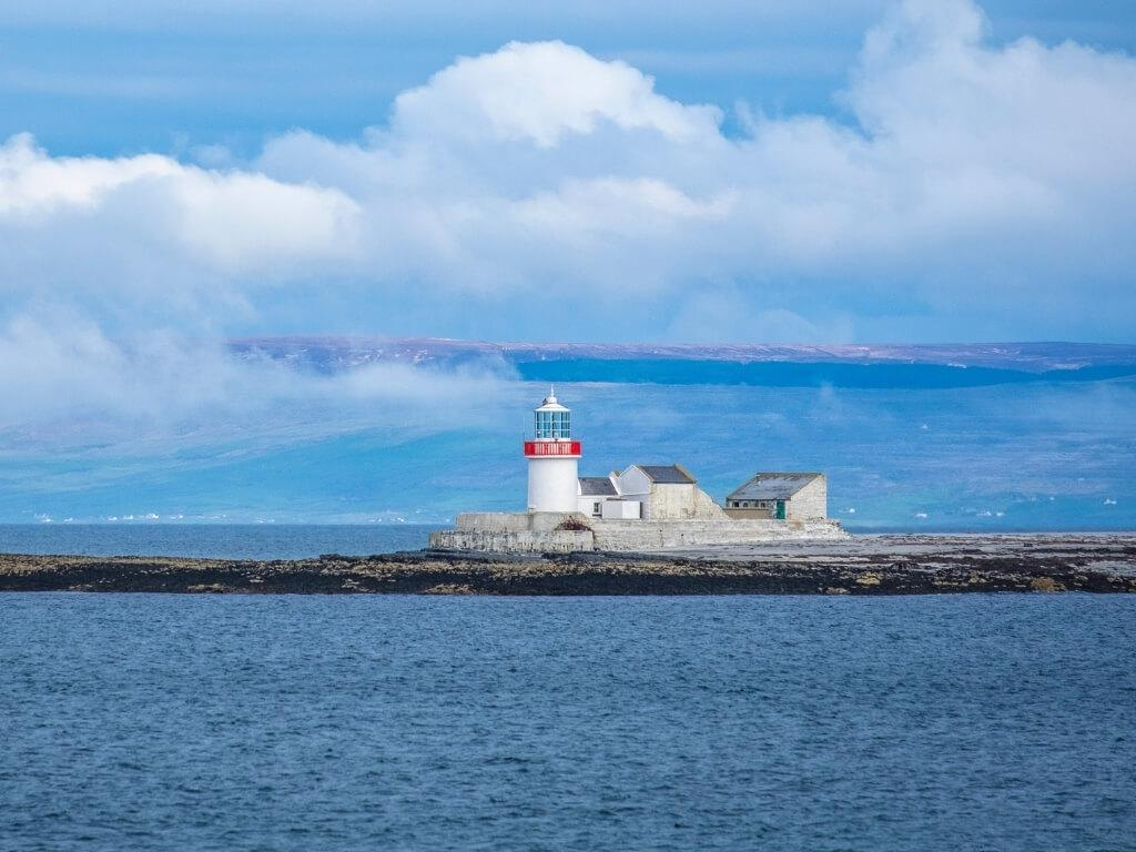 A picture of the The Eeragh Lighthouse on the Aran Islands, Galway surrounded by water and with mountains in the background