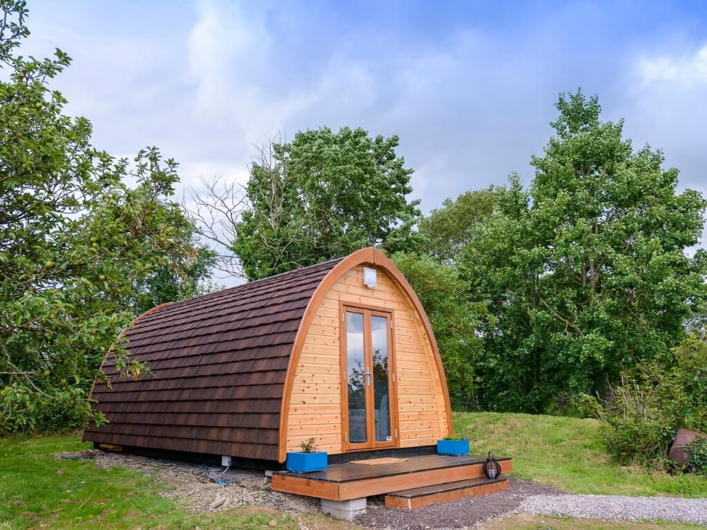 A picture of one of the glamping pods with trees behind it at Farmyard Lane Glamping