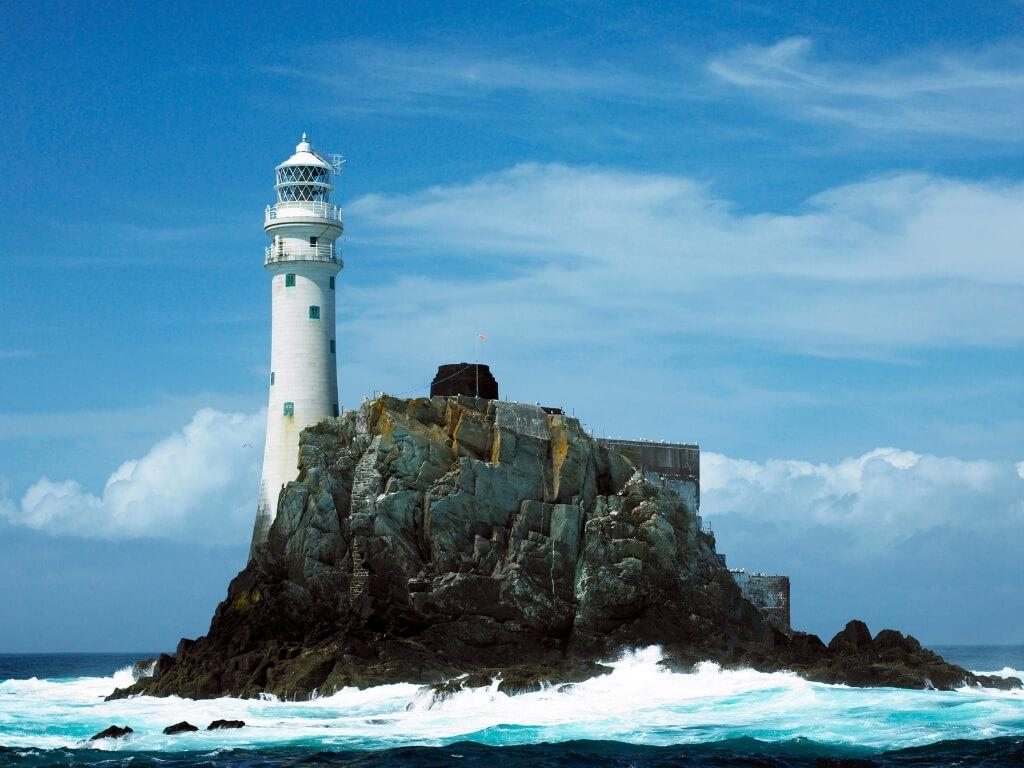 A picture of the tall Fastnet Lighthouse standing on its rocky island off-shore, one of the best lighthouses in Ireland to see
