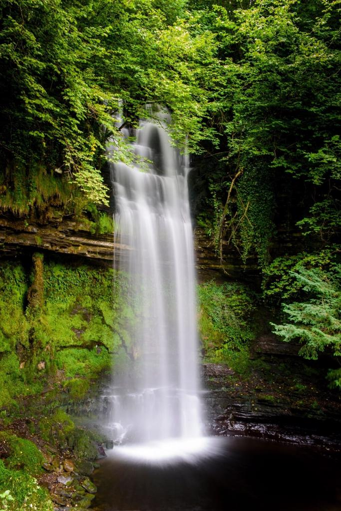 A picture of the beautiful Glencar Waterfall surrounded by lush green trees and shrubs