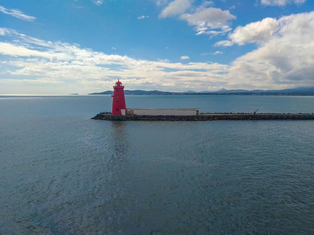 A picture of the distinctive red Poolbeg Lighthouse in Dublin bay with view across to Sugar loaf Mountain in Wicklow in the background
