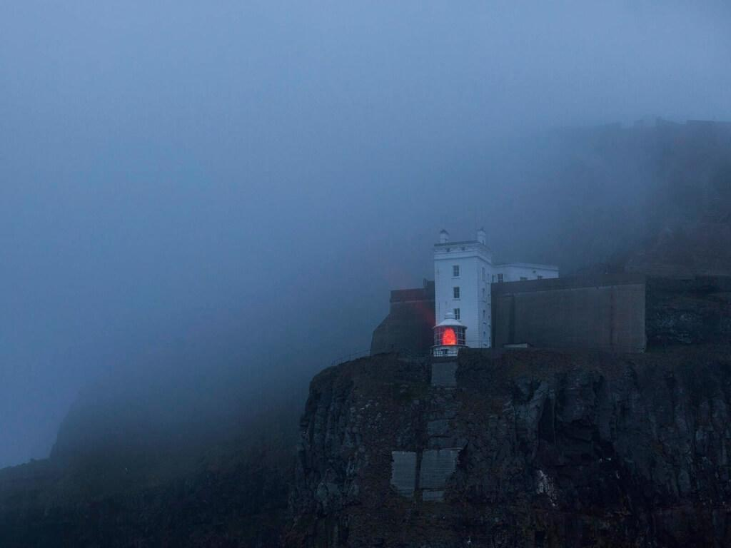 A picture of the Rathlin West Lighthouse shining its upside down beacon in foggy conditions