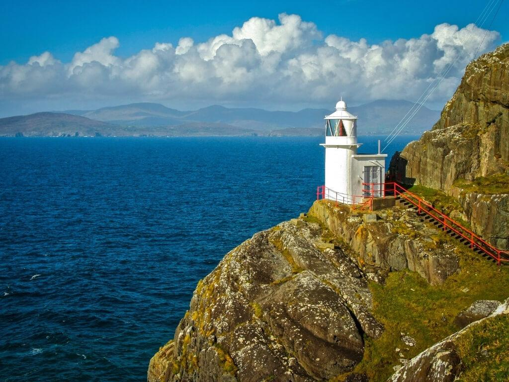 A picture of the white tower of Sheep's Head Lighthouse looking out across the sea with mountains in the far distant background