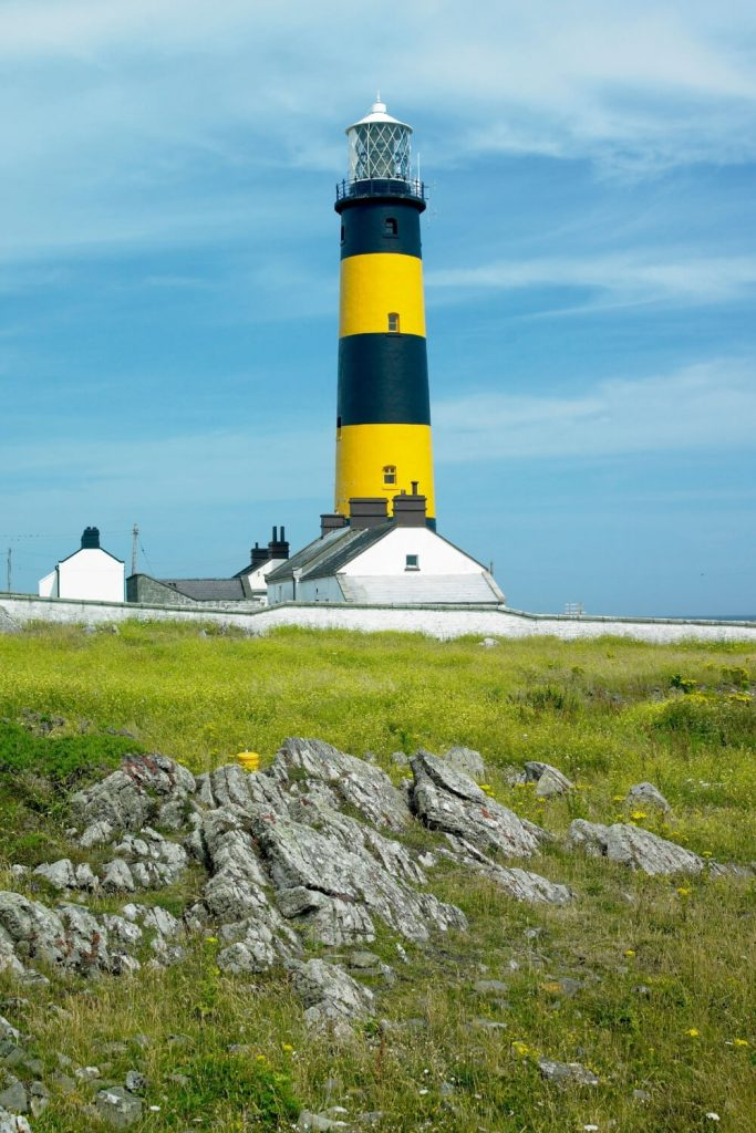 A picture of the striking black and yellow The St John's Point Lighthouse in County Down with blue skies overhead with whispy clouds