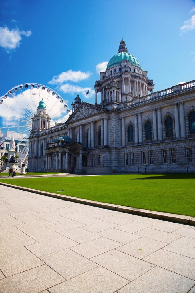 A picture of Belfast City Hall with a Ferris Wheel behind it, green grass in front and blue skies overhead