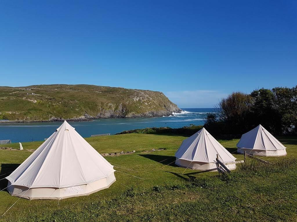 A picture of some of the bell tents of Chleire Haven Glamping overlooking the sea