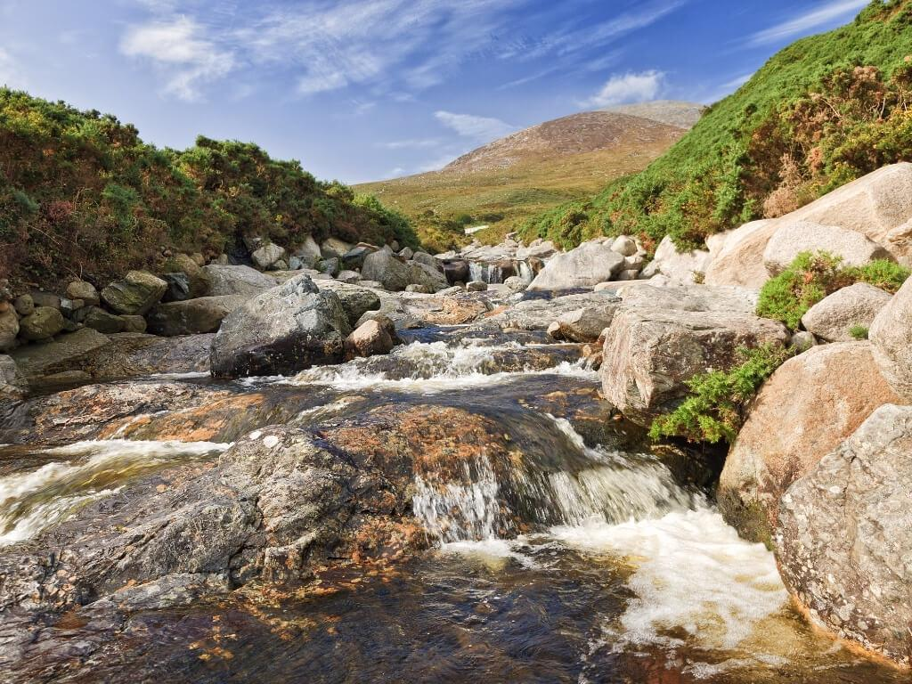 A picture of a gentle river slowing between rocks with hills in the background in the Mourne Mountains in Northern Ireland