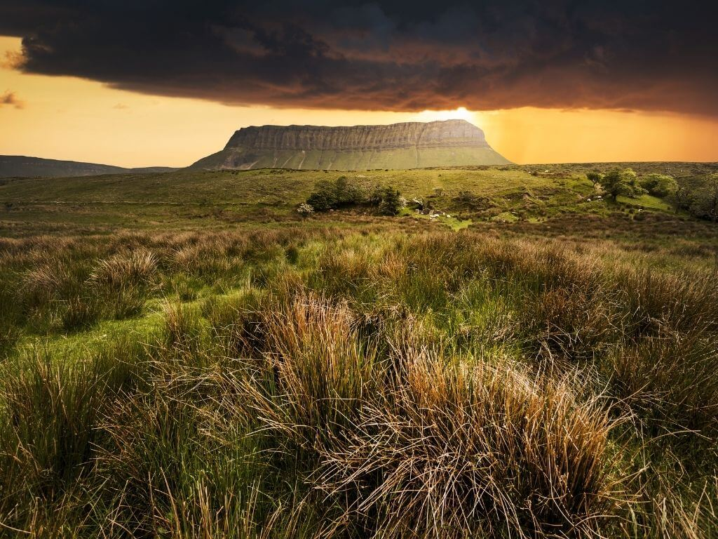 A picture of a dark cloud sitting over Benbulbin, Sligo, Ireland with the sun behind it