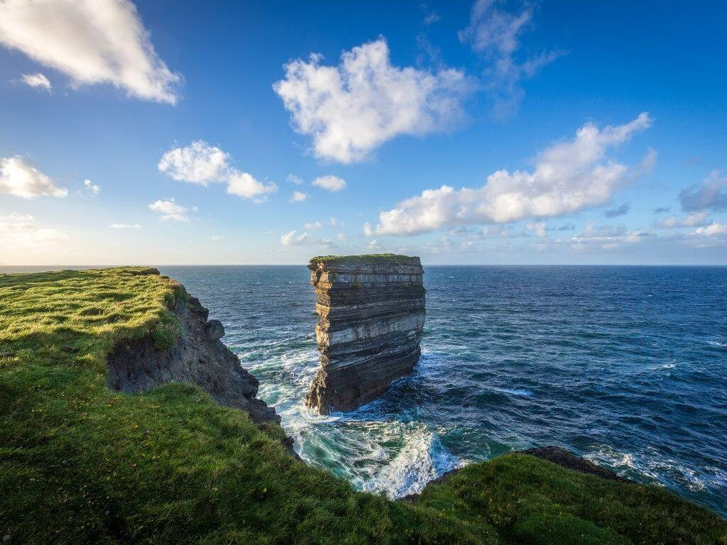 A picture of the sea stack of Downpatrick Head in County Mayo with waves crashing around it and blue skies overhead