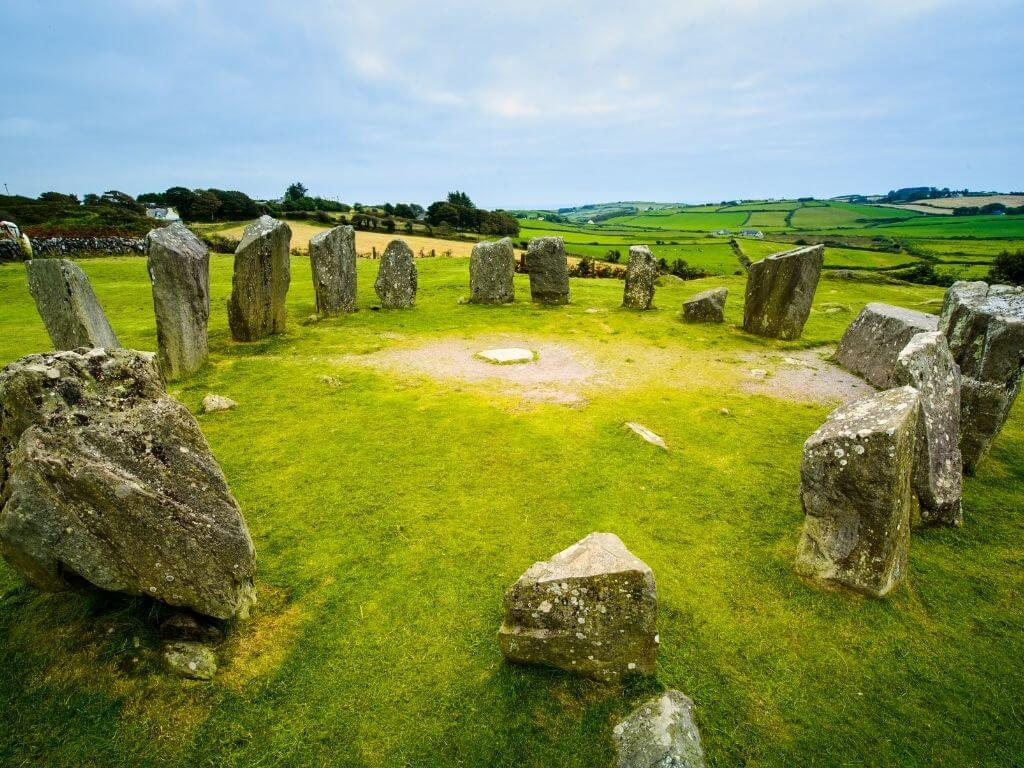 A picture of the Drombeg Stone Circle in County Cork, with lush green fields in the background