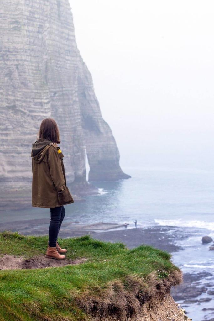 A picture of a woman looking at cliffs along the Irish coast
