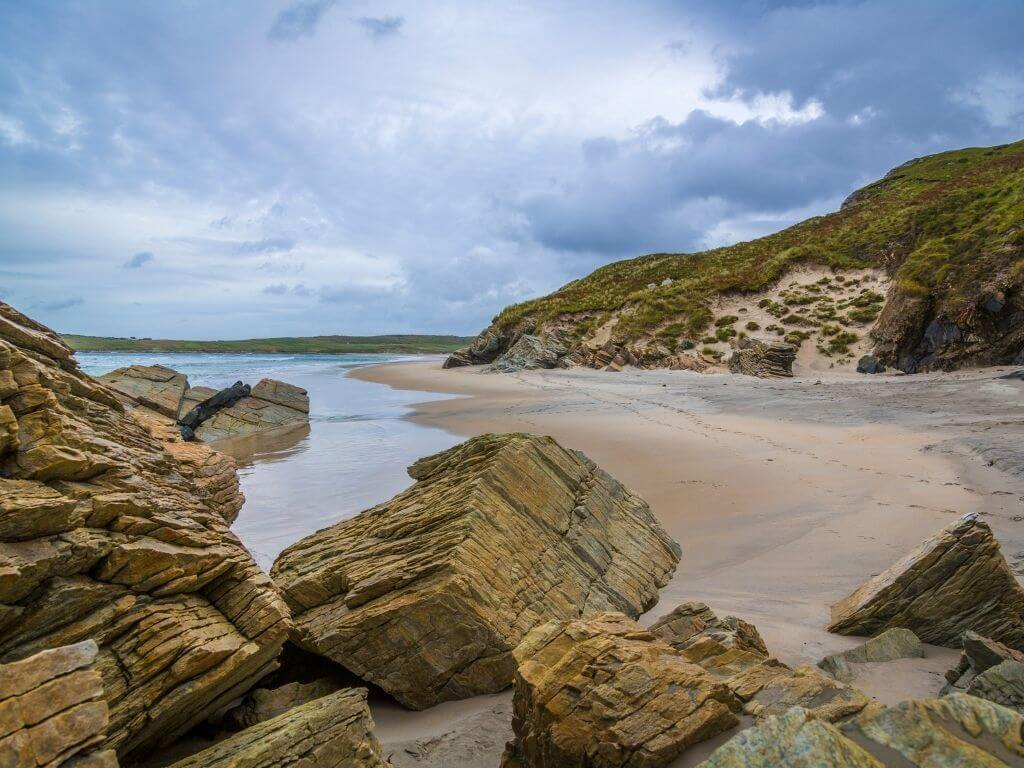 A picture of the beach and rocky outcrop at Maghera Beach in County Donegal