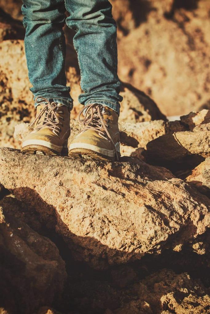 A picture of a kid in hiking boots standing on some rocks