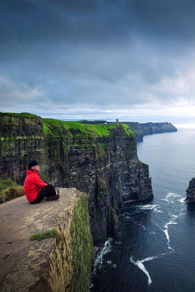 A picture of a man enjoying views of the Cliffs of Moher