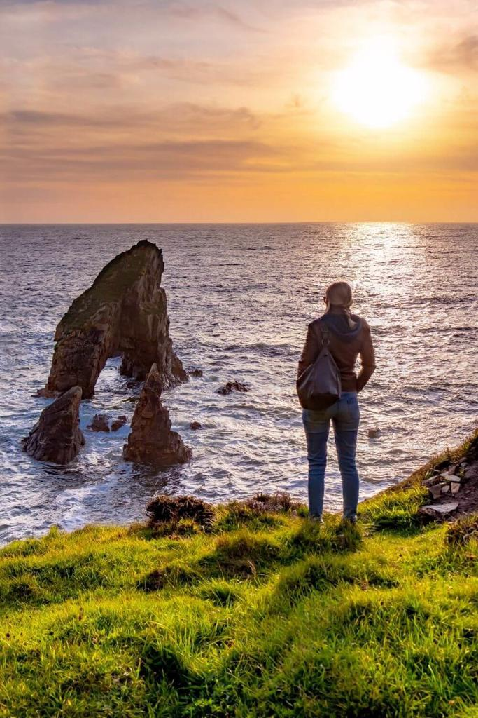 A woman in jeans and a jacket standing at the coast edge looking at the Crohy Sea Stacks in Ireland