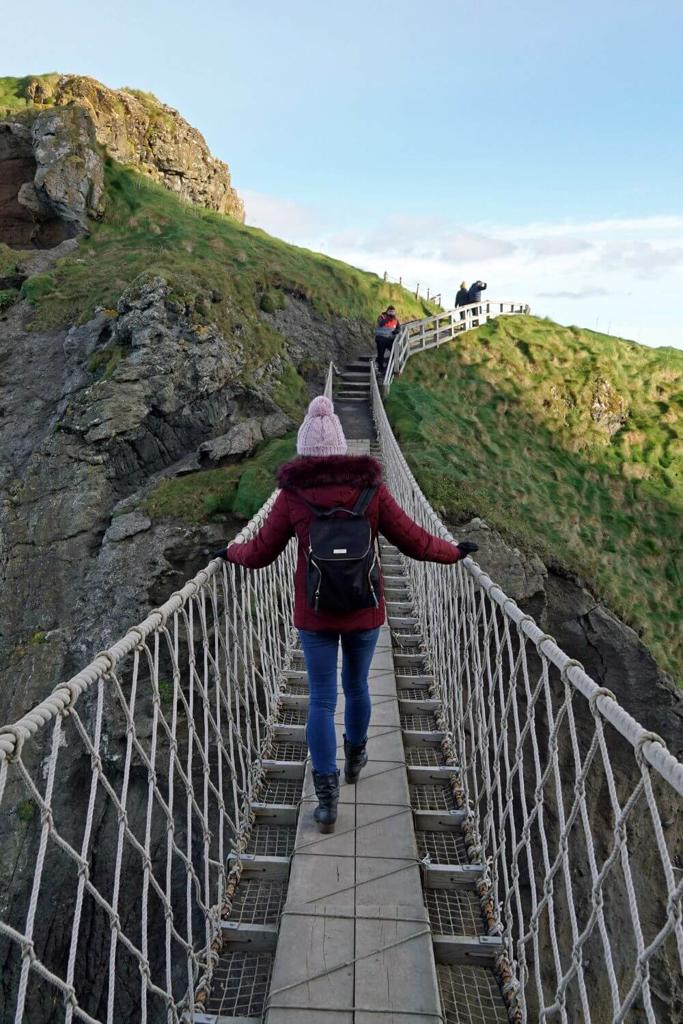 A picture of a woman in a wine coat and woollen hat crossing the Carrick-a-Rede Rope Bridge in Northern Ireland