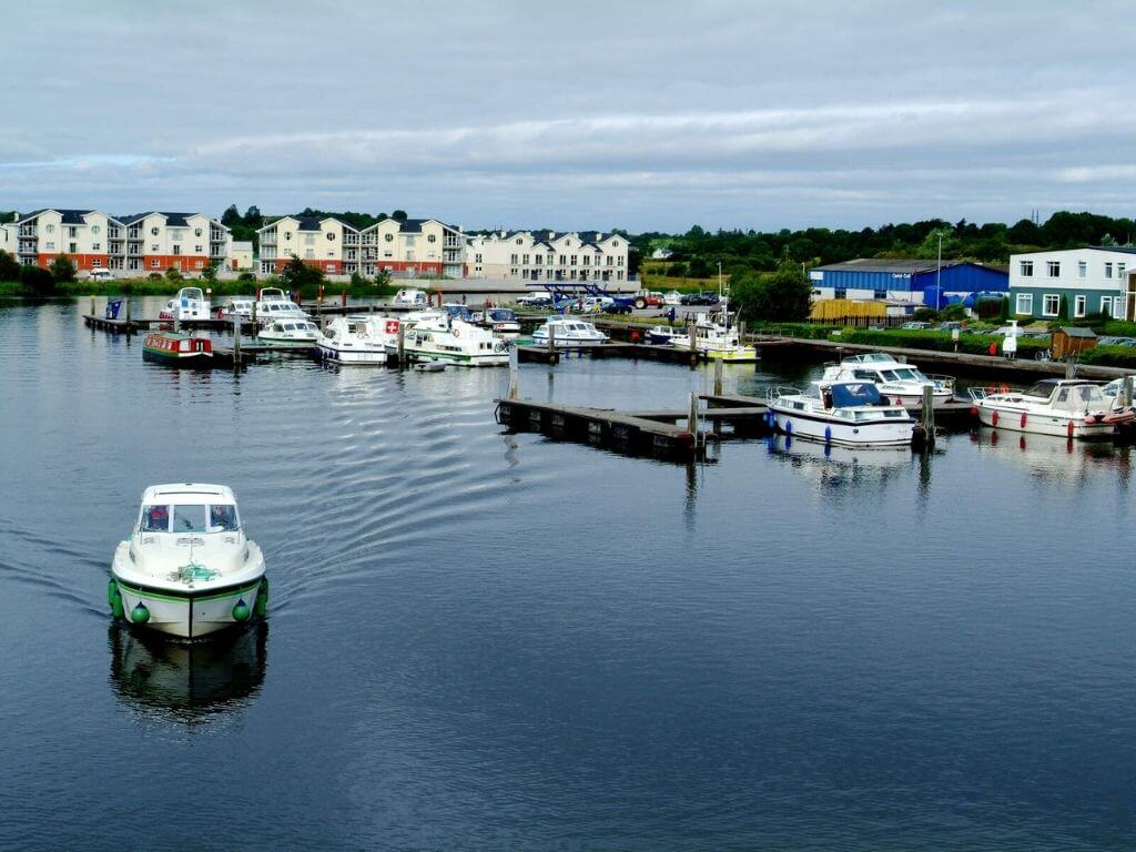 A picture of the Carrick-on-Shannon Marina with boats moored and one moving through the water