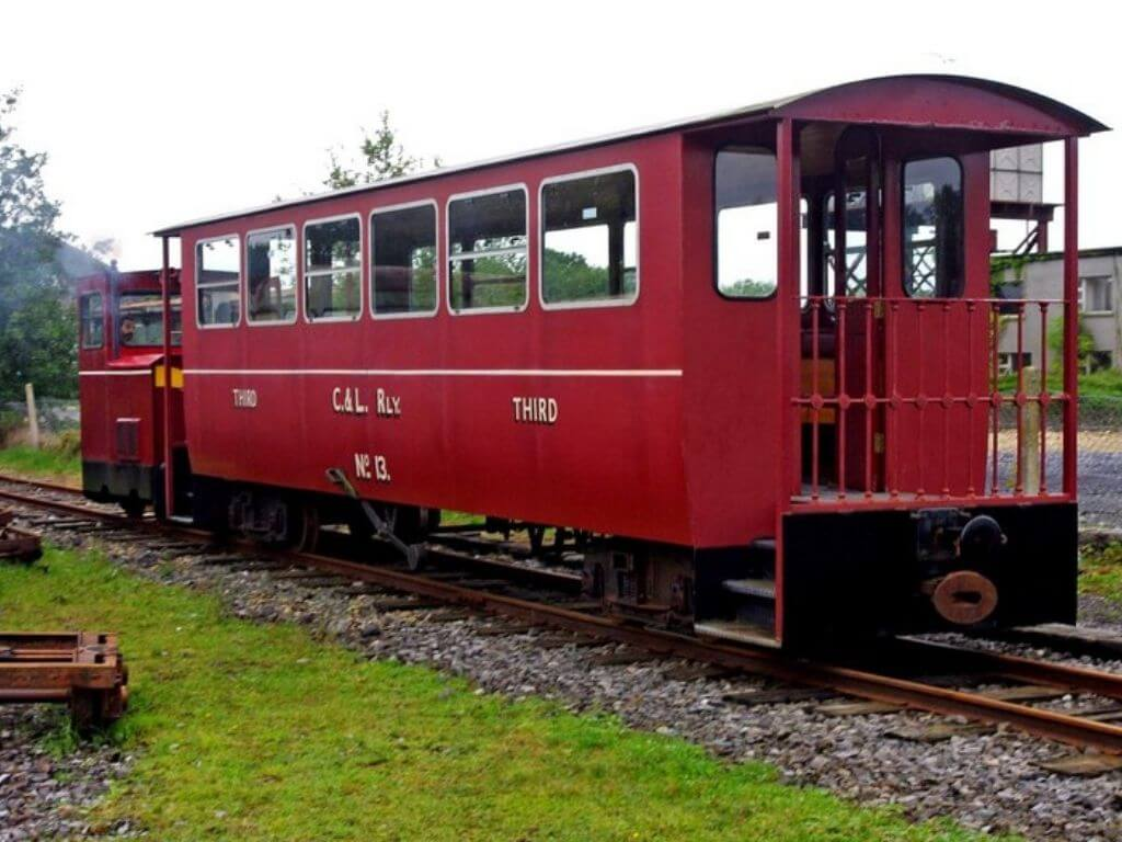 A picture of a red train carriage and engine at the Cavan & Leitrim Railway