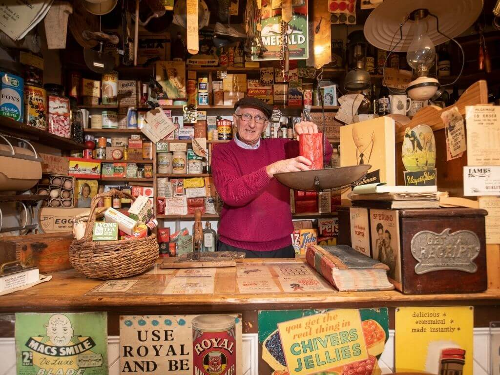 A picture of one of the owners of the Derryglad Folk Museum in the rural shop reconstruction
