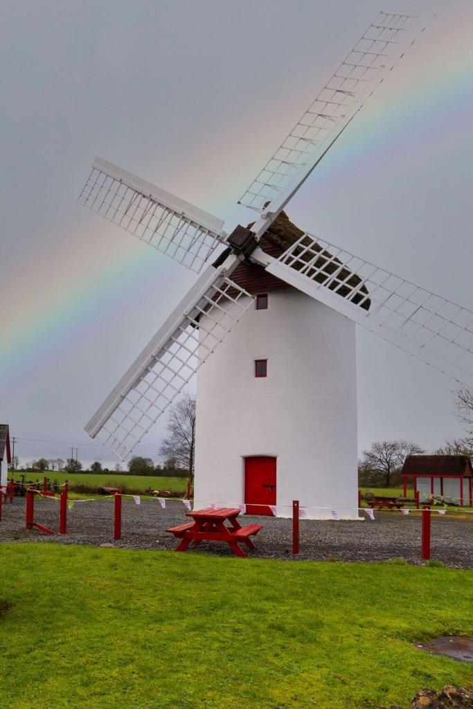 A picture of the Elphin Windmill in Roscommon with a grey sky and rainbow behind it