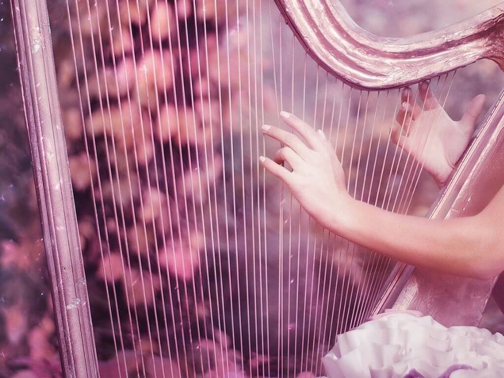 A picture of a set of hands (of a fairy) playing a harp symbolising the Aibell from Irish folklore
