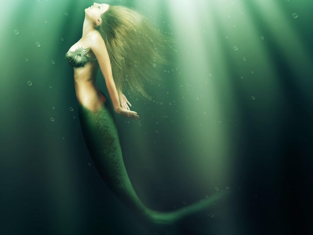 A picture of a mermaid in the water with blonde hair and a green tail