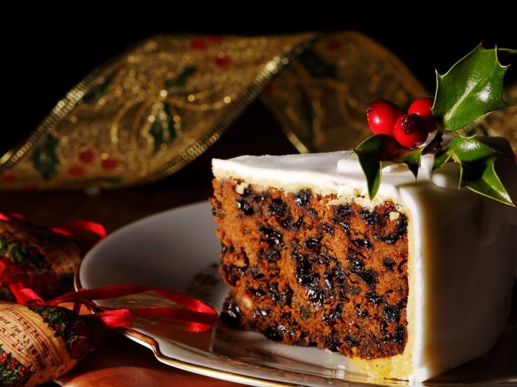A picture of a slice of traditional Christmas Cake decorated with white icing and holly